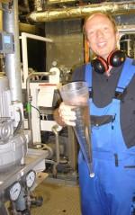 """Achim Schüler (leitender technischer Offizier der SONNE) mit gereinigtem Abwasser aus dem bordeigenen """"Klärwerk""""."""